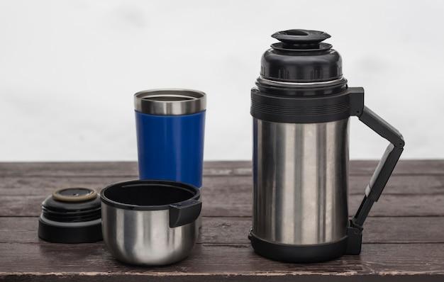 Außenthermosflasche mit kaffee und einem reisebecher auf der bank im winter, draufsicht.