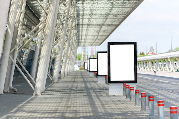 Außenwerbeplakat neben den säulen eines modernen gebäudes.