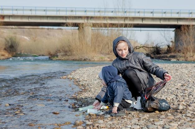 Außer umweltkonzept sammeln ein kleiner junge und seine mutter müll und plastikflaschen am strand, um sie in den müll zu werfen.