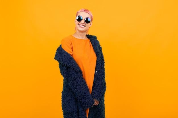 Außergewöhnlich schöne frau mit kurzen rosa haaren im dunklen mantel und sonnenbrille lächelt isoliert auf orange hintergrund.