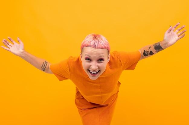Außergewöhnlich schöne frau mit kurzen rosa haaren und großem tattoo auf ihrer hand versteht etwas nicht isoliert auf orange hintergrund