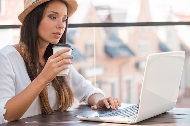 Außerhalb arbeiten. schöne junge frau mit flippigem hut, die am laptop arbeitet und lächelt, während sie draußen sitzt