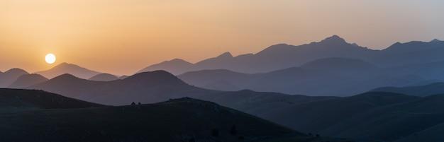 Aussichtspunkt für den sonnenuntergang auf der silhouette der felsigen berge. campo imperatore, gran sasso, apennin, italien. die sonne des klaren himmels platzte auf einem dramatischen bergkamm.