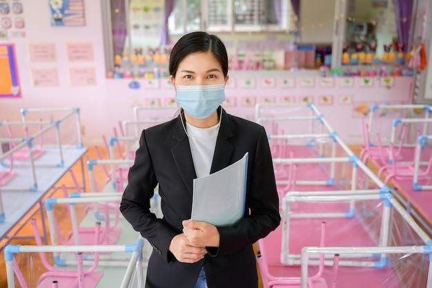 Aussparungsschule für kinder und junge asiatische lehrer tragen masken, um die verbreitung von covid 19 in einem klassenzimmer ohne schüler zu verhindern.