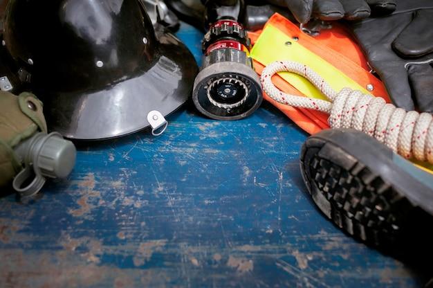 Ausstattung des feuerwehrmanns auf altem tabellenhintergrund, feuerausrüstungskonzept.