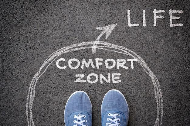 Ausstieg aus dem komfortzonenkonzept. füße in blue jeans-sneakers stehen in der komfortzone des kreises und der pfeil nach außen kreidet auf dem asphalt