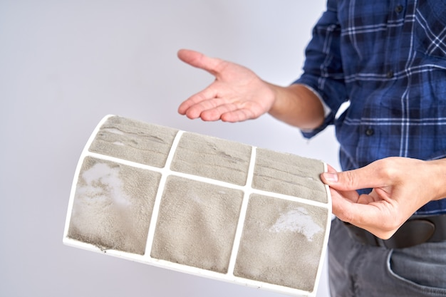 Austausch- und reinigungskonzept für die klimaanlage zu hause. professioneller fixierer zeigt verschmutzte filter aus der nähe