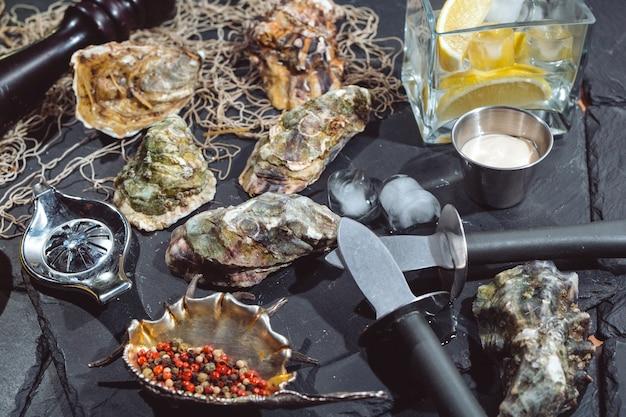 Austern auf steinplatte mit eis, zitrone, fischernetz, pfeffer und messer.