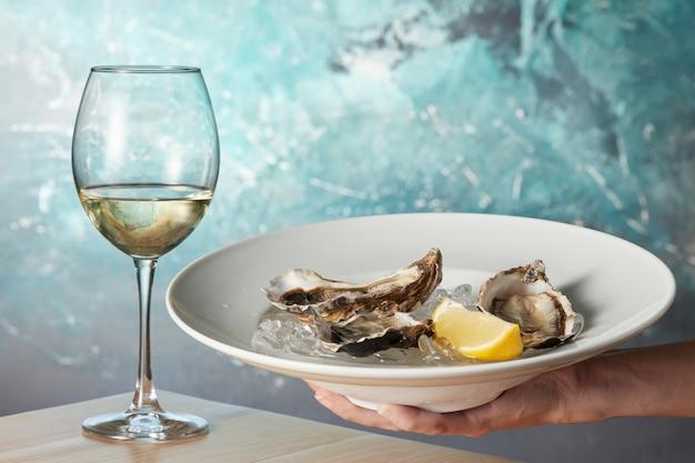 Austern in einem weißen teller mit zitrone und einem glas wein auf einem holztisch lokalisiert auf weiß