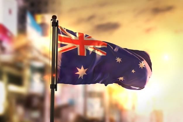 Australien flagge gegen stadt verschwommen hintergrund bei sonnenaufgang hintergrundbeleuchtung