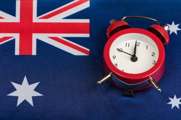 Australien-flagge und vintage-wecker hautnah. zeit, englisch zu lernen. der australische akzent.