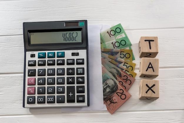 Australische dollar-banknoten mit holzwürfeln und taschenrechner