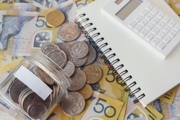 Australisches geld im glasgefäß, aud mit taschenrechner, notizbuch, einsparungskonzept