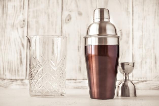 Auswahl an bargeschirr - mischglas, cocktail-shaker und jigger auf weißem holzhintergrund