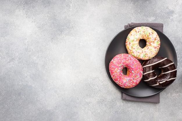 Auswahl an donuts in der glasur auf einem teller, draufsichtkopierraum.