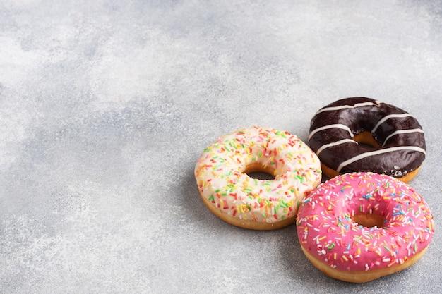 Auswahl an donuts in zuckerguss auf einem grauen betontisch, kopierraum.