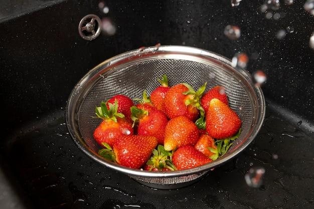 Auswahl an erdbeeren, die gewaschen werden