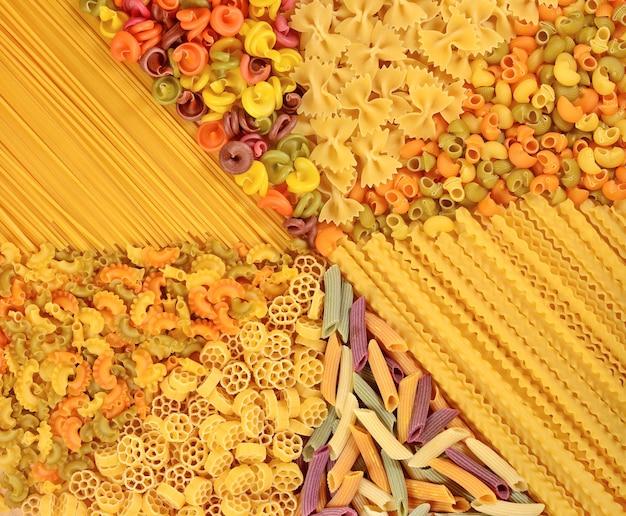 Auswahl an farbigen ungekochten italienischen nudeln als hintergrundtextur