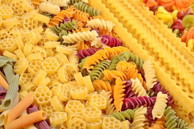 Auswahl an farbigen ungekochten italienischen nudeln hautnah als hintergrund