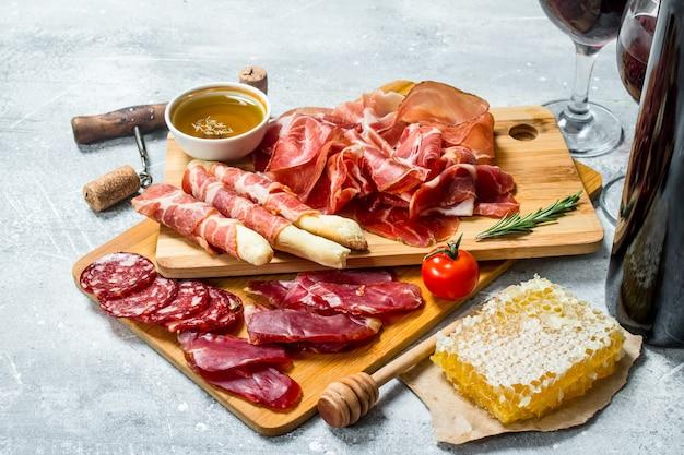 Auswahl an fleischsnacks mit rotwein auf einem rustikalen tisch.
