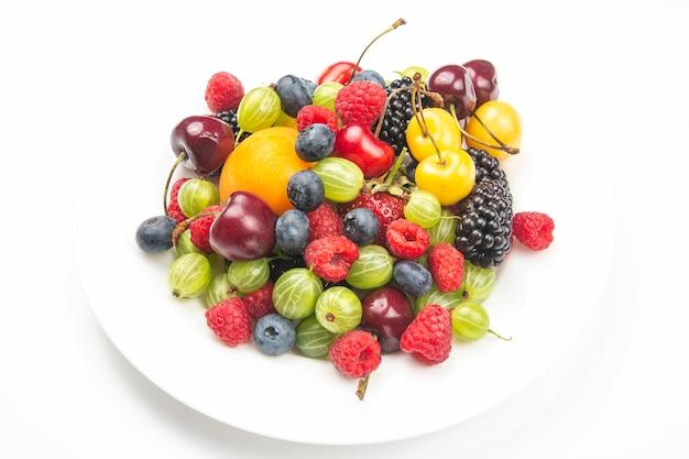 Auswahl an frischen beeren auf einem weißen teller. nützliches vitamin gesundes essen obst. gesundes gemüsefrühstück