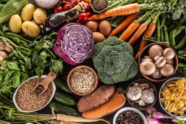 Auswahl an frischen lebensmitteln und gesunder ernährung: gemüse, obst, hülsenfrüchte und getreide auf einem betontisch - ansicht von oben.