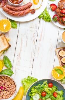 Auswahl an frühstücksoptionen. englisches frühstück, würstchen, spiegeleier, speck, salat, müsli