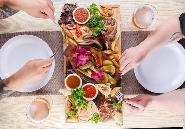 Auswahl an gebratenem fleisch, kartoffeln, würstchen, gurken, tomaten, paprika, kräutern, lavash auf einem holztablett auf dem tisch. draufsicht.