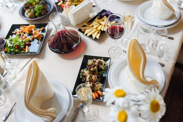 Auswahl an gerichten, auberginenröllchen, käsescheiben, weinschale, gläsern, servietten, tellern auf einem weißen holztisch. sitzordnung bei tisch.