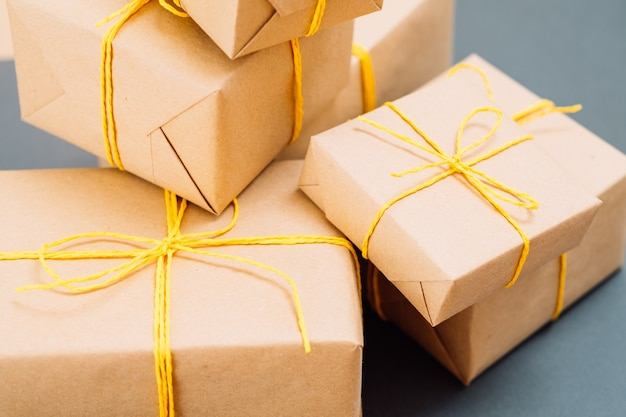 Auswahl an geschenken, eingewickelt in bastelpapier, gebunden mit einer gelben schnur. feierliche geschenke oder belohnung an festlichen feiertagen. pakete an der blauen wand.