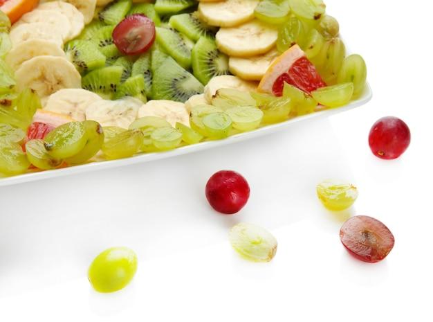 Auswahl an geschnittenen früchten auf teller, isoliert auf weiß