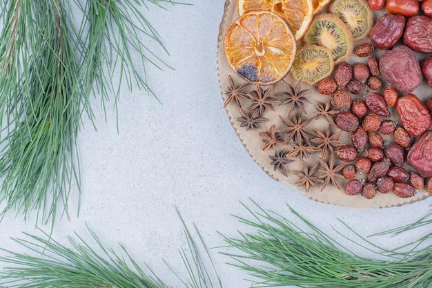 Auswahl an getrockneten früchten und nelken auf holzstück.