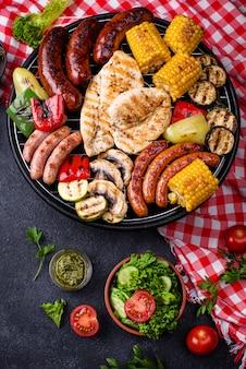Auswahl an grillwürsten, fleisch und gemüse. picknick gegrilltes konzept
