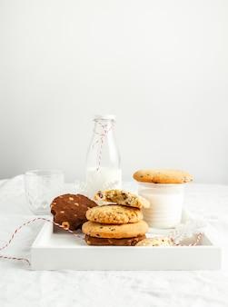 Auswahl an hausgemachten keksen und milch auf holztablett