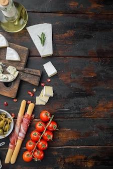 Auswahl an käse- und fleisch-vorspeisen auf dunklem holz, flach gelegt