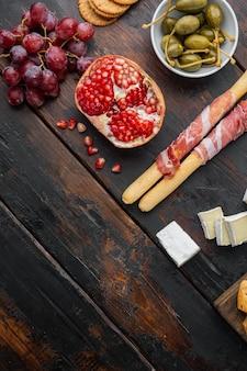 Auswahl an käse- und fleisch-vorspeisen auf dunklem holztisch, flach gelegt