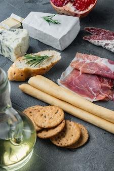 Auswahl an käse- und fleisch-vorspeisen auf grauem tisch