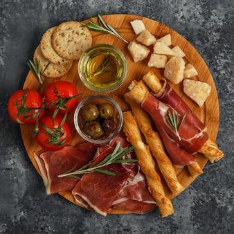 Auswahl an käse- und fleisch-vorspeisen. schinken, parmesan, brotstangen, oliven, tomaten auf holzbrett.