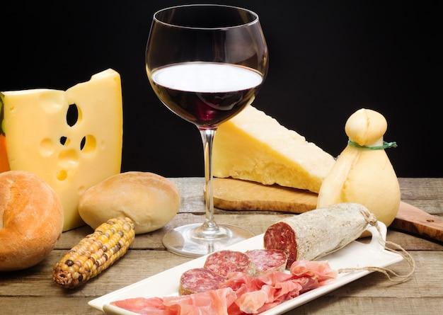 Auswahl an käse und schinken mit einem glas rotwein