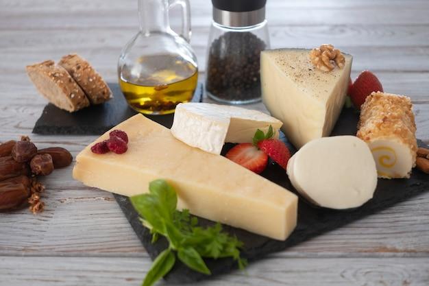 Auswahl an käsescheiben mit früchten pfeffer und olivenöl auf holztisch