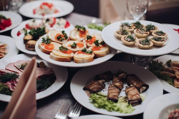 Auswahl an kalten snacks auf tellern beim bankett serviert. sandwiches mit kaviar, auberginenröllchen, törtchen mit fleisch.