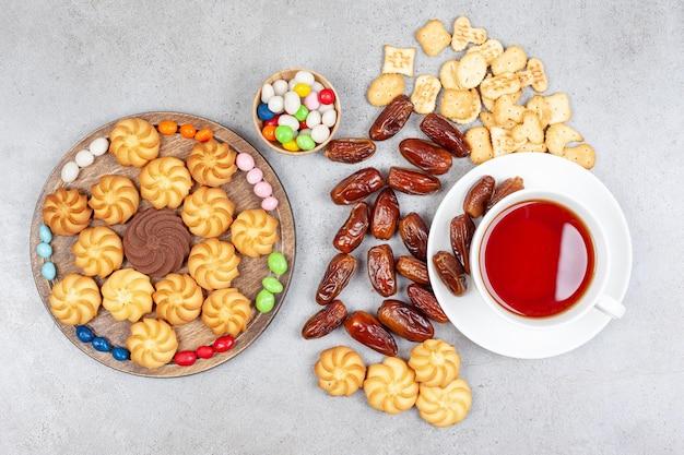 Auswahl an keksen, keksen, datteln und bonbons mit einer tasse tee auf marmoroberfläche.