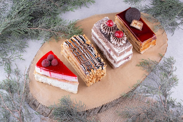 Auswahl an kuchenstücken auf holzstück. foto in hoher qualität