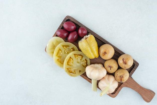 Auswahl an leckerem fermentiertem gemüse auf holzbrett.