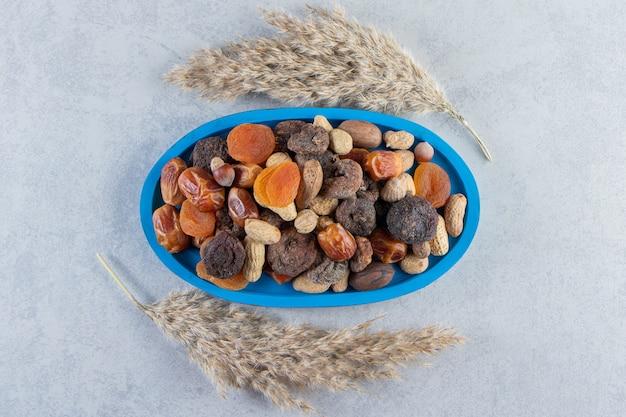 Auswahl an leckeren trockenfrüchten und nüssen auf steinhintergrund.