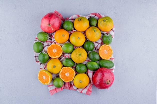 Auswahl an mandarinen, feijoas und granatäpfeln auf marmorhintergrund. foto in hoher qualität