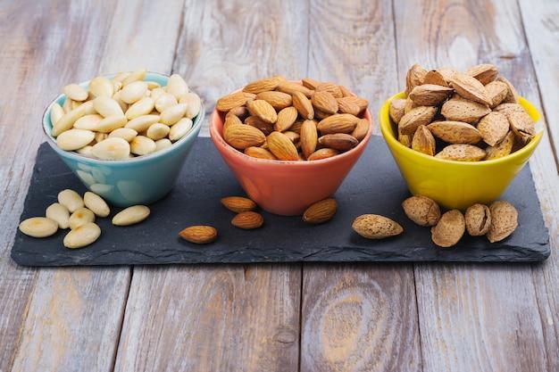 Auswahl an mandelnüssen - geschält und gebraten, ungeschält und mandeln in muscheln