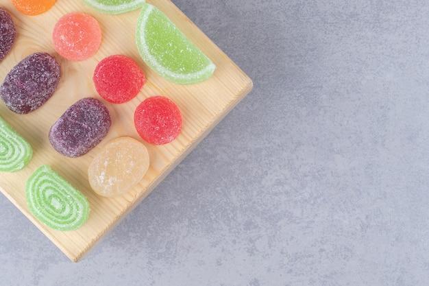 Auswahl an marmeladen auf einem holzbrett auf marmortisch.