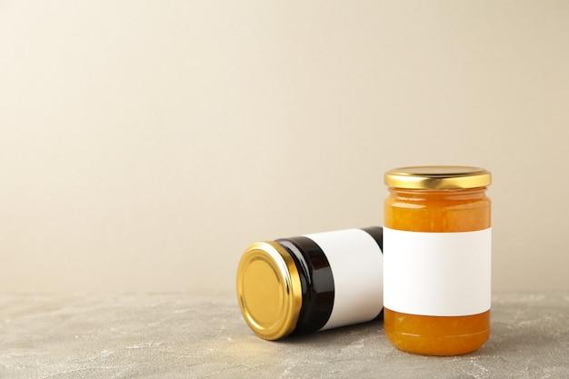 Auswahl an marmeladengläsern. gläser mit leerem etikett auf grau. ansicht von oben