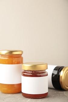 Auswahl an marmeladengläsern. gläser mit leerem etikett auf grau. vertikales foto